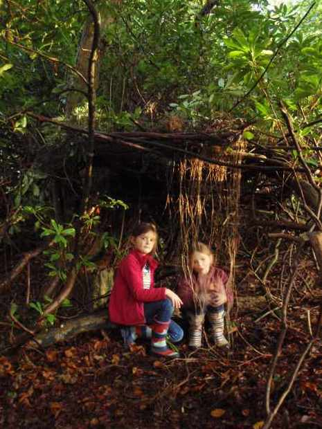 Two girls sit talking outside their den