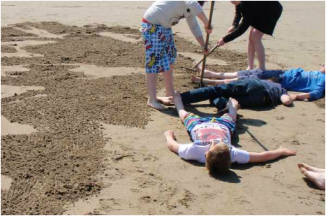 Young people lying on the sand while others rake the sand around them