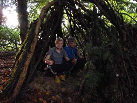 Two boys sitting in their den made of sticks