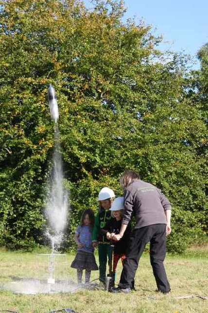 Lemonade bottle rocket flying leaving a jet of water behind it. Part of the Rocket Lab activity from the Freelance Ranger