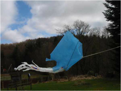 Blue Plastic bag kite flying with trees in the background